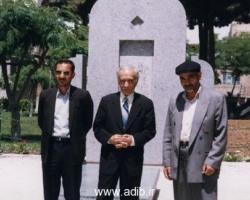 ادیب برومند در کنار آرامگاه کلنل محمد تقی خان پسیان با دو تن از کارکنان باغ نادری